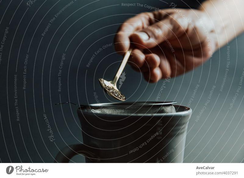 Eine alte Hand, die einen Tee über einen dunklen Hintergrund mit Kopierraum und dunklen Tönen vorbereitet trinken Tasse Wasser heiß Frau Küche Person eingießen