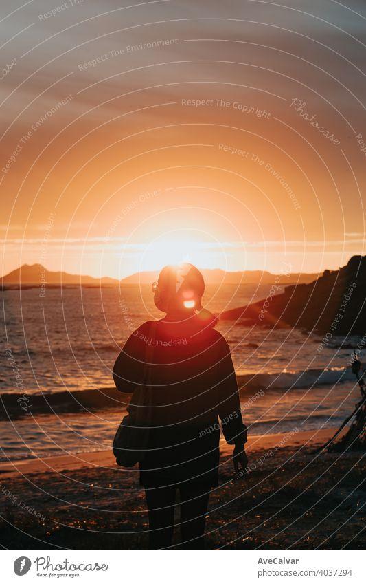 Ein Reisender vor einem bunten Sonnenuntergang am Strand mit Gesichtsmaske, Wellness-Konzept, Leben und Freiheit Frau Glück Silhouette Menschen Inspiration