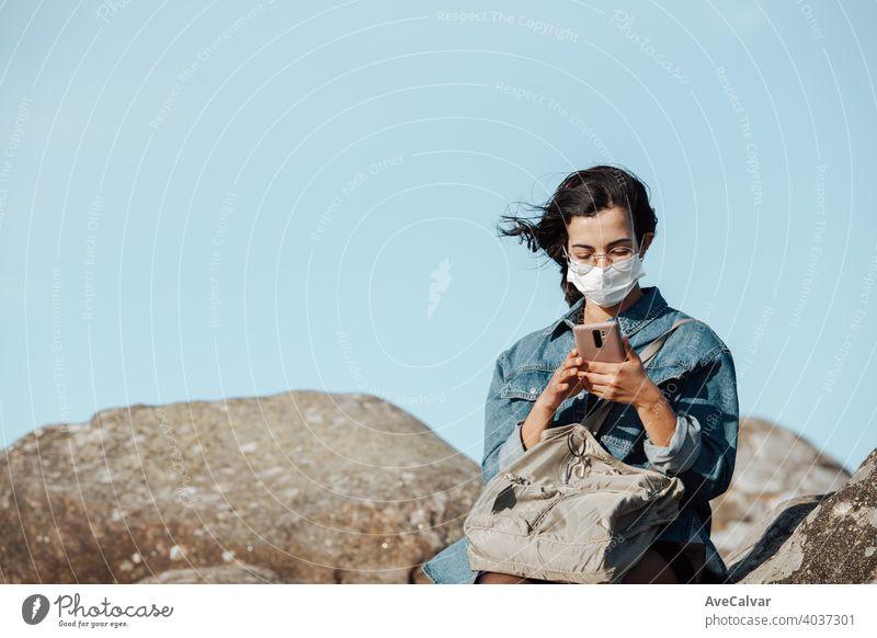 Eine junge Frau, die eine Maske trägt, überprüft sein Telefon, während der Wind mit Kopie Raum weht Mobile Menschen Natur Person Lächeln Glück schön Funktelefon