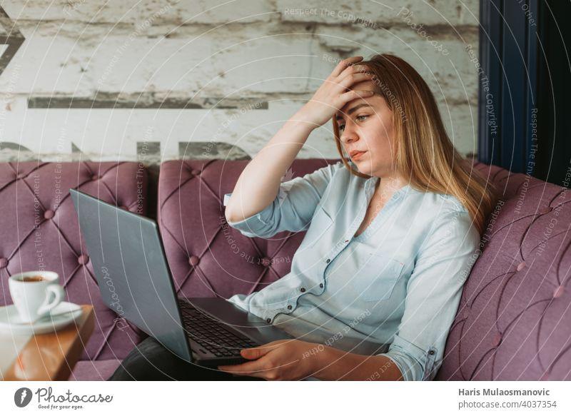 Frau mit Kopfschmerzen bei der Arbeit am Laptop, stressige Arbeit, schlechte Nachrichten per E-Mail Erwachsener Rückenhaltung Haltungsfehler schön Business