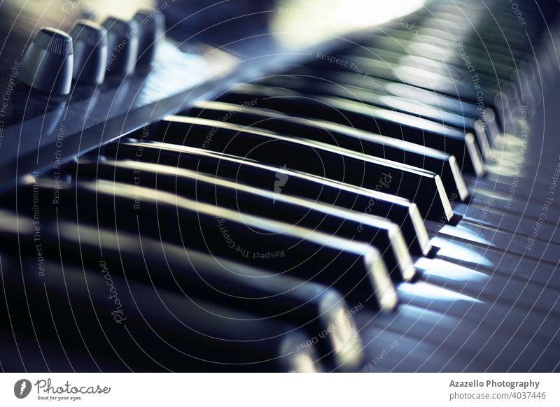 Elektrische Klaviertastatur in Unschärfe. Klaviertastatur mit Tageslichtreflexionen. akustisch Audio Hintergrund Band schwarz blau Bokeh Kind Akkord Klassik