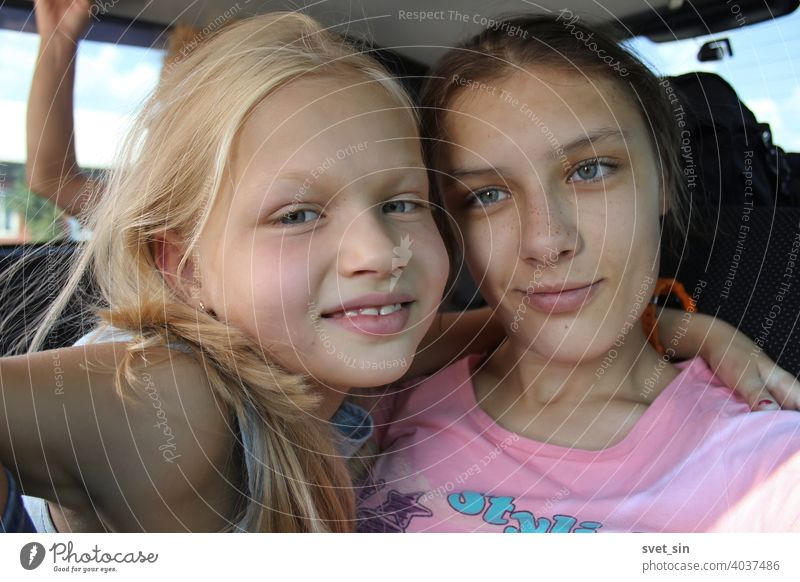 Lächelnde Schwestern auf einer Autofahrt: blond und braunhaarig. Zwei Mädchen unterschiedlichen Alters lächeln, umarmen sich, im Inneren des Autos. Teenager