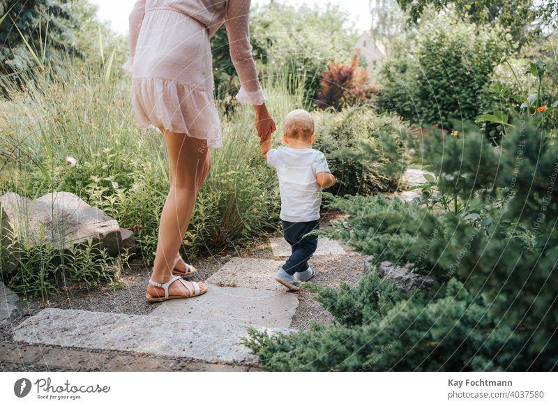 Kleinkind, das mit Hilfe seiner Mutter im Freien laufen lernt bezaubernd Baby Bonden Junge Kind Kindheit krabbeln kriechend niedlich Gefühle erkunden erkundend