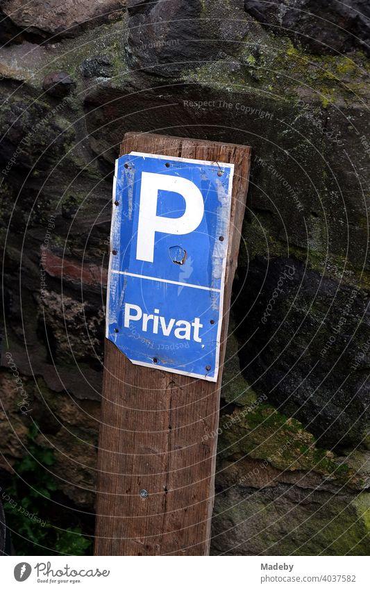 Heruntergekommenes Parkplatz Schild bei Regen vor altem Mauerwerk aus Naturtstein in Wettenberg Krofdorf-Gleiberg bei Gießen in Hessen Parken privat