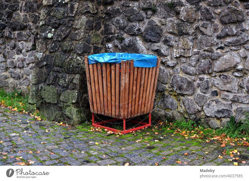 Mülleimer aus braunem Holz ausgelegt mit blauem Plastiksack vor altem Mauerwerk im Burghof von Burg Gleiberg in Wettenberg Krofdorf-Gleiberg bei Gießen in Hessen