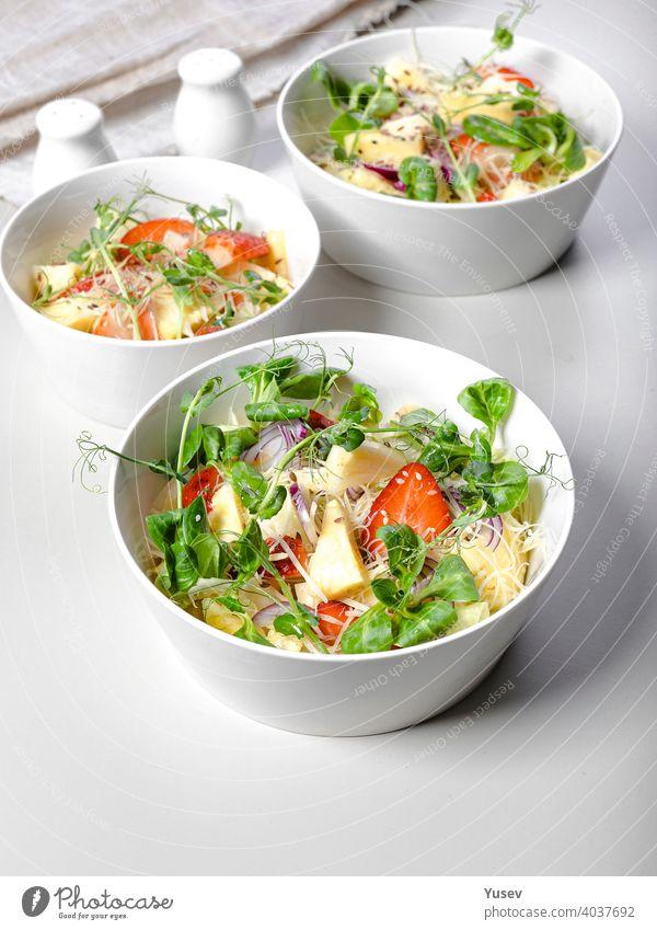 Obstsalat mit Erdbeeren, Ananasstücken, Kräutern, roten Zwiebeln und Käse in weißen Keramikschalen auf einem hellen Hintergrund. Ideen und Rezepte für eine gesunde Ernährung. Vegetarisches Essen. Vertikale Aufnahme