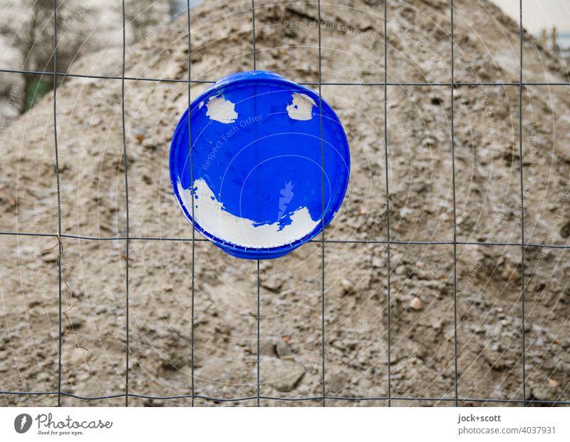 freundlicher Deckel am Drahtzaun Sandhaufen Plastikdeckel Smiley Baustelle befestigt einfach Straßenkunst Kreativität Kreis Inspiration
