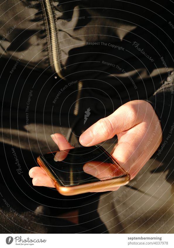 Handy in einer Hand Handy bronzefarben Männerhand hell schwarze Jacke schwarze Hose Fingerspiegelung im Handy