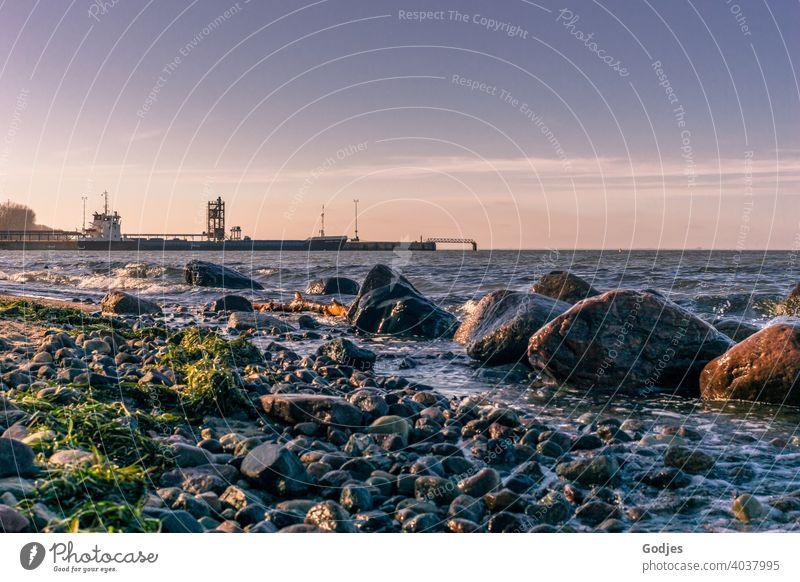 Strand mit Felsen in der Nähe eines Industriehafens Hafen Kran Himmel Abenddämmerung Wolken Anlegestelle Container Güterverkehr & Logistik Containerterminal