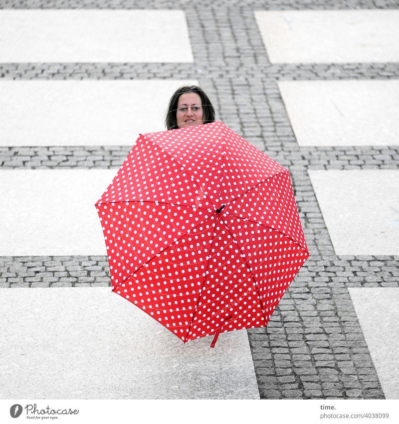 Frau hinter Schirm voraus Kopf verstecken Platz Steinweg neugierig lächeln linien rot skurril Sonnenschirm regenschirm