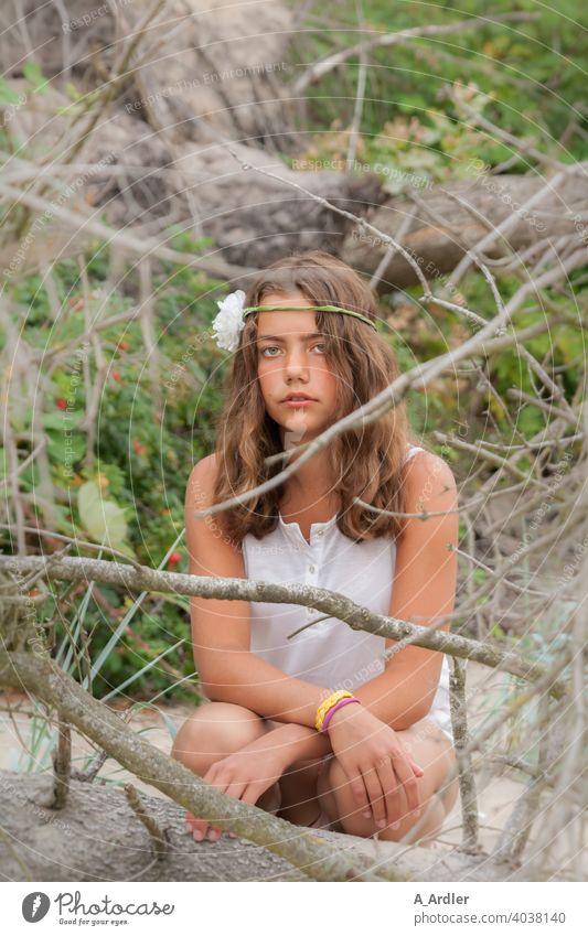 Junges Mädchen mit Blume im Haar sitzt am Strand Urlaub Frau jubg schön sommer Ferien & Urlaub & Reisen Sand Freude Erholung Gebüsch Sträucher Äste Bäume Grün