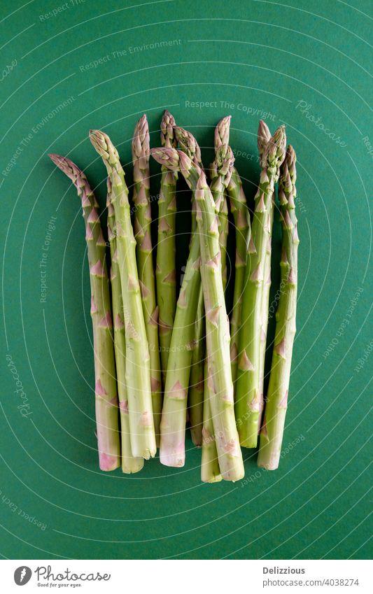Ein Bündel frischer grüner Spargel auf einem grünen Hintergrund, Kopierraum, vertikal Grünspargel Veganer flache Verlegung Kochzutaten Lebensmittel Gesundheit