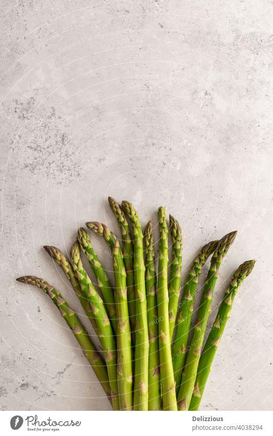 Ein Bündel frischer grüner Spargel auf grauem Hintergrund, Kopierraum, vertikal Grünspargel Veganer flache Verlegung Kochzutaten Gesundheit Vegetarier