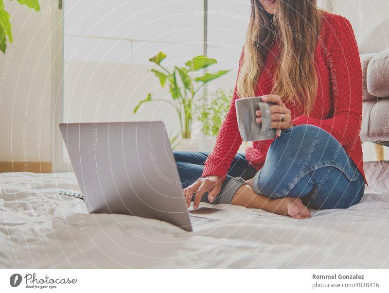Eine Frau, die Tee trinkt, auf dem Boden einer Wohnung sitzt und sich Notizen macht, hat einen Laptop vor sich aufgeklappt. Home-Office-Konzept. Bietet Kaffee an. Konzept kreative Arbeit zu Hause. Selektiver Fokus.