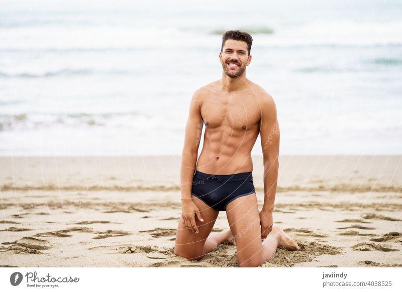 Hübscher Mann auf den Knien auf dem Sand des Strandes sexy männlich muskulös gutaussehend Gesundheit Wasser Menschen passen MEER Model Bauchmuskeln Urlaub
