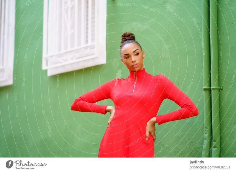 Junge gemischte Frau in rotem Kleid vor einer grünen Wand schwarz Schleife ernst Frisur Behaarung Model Schönheit hübsch Porträt Mädchen jung Person Dame Sommer