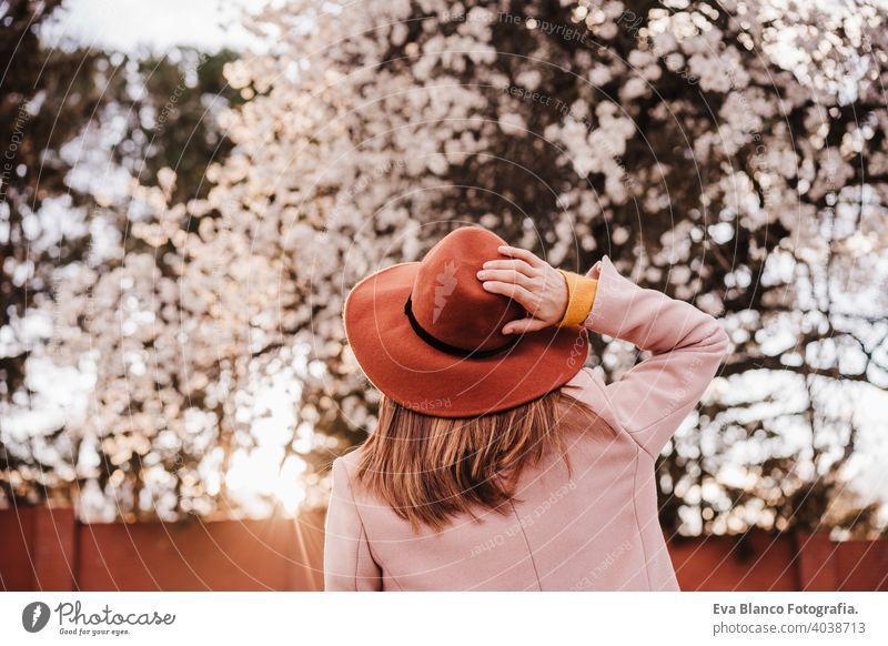 Rückenansicht Porträt der jungen Frau trägt modernen Hut bei Sonnenuntergang im Park. schönen Mandelbaum Blumen Hintergrund. Frühling und Blüte Bäume im Freien