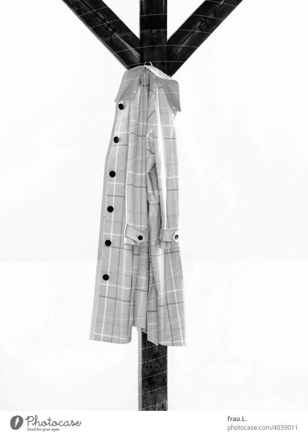 Am Dachbalken hängt ein Regenmantel Mode Übergangsmantel Innenaufnahme Mantel Stützbalken kariert Blitzlichtaufnahme