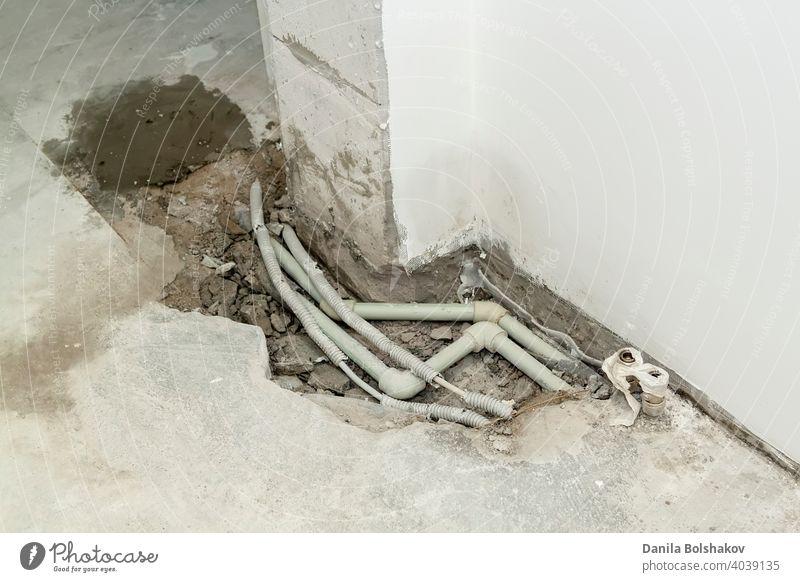 Reparatur von grauen Kunststoff-Polypropylen-Kanalrohren in einem Loch im Zementboden einer Wohnung. Konzept für den Austausch von Rohren, Wasserleckagen, Übertragung der Wasserversorgung