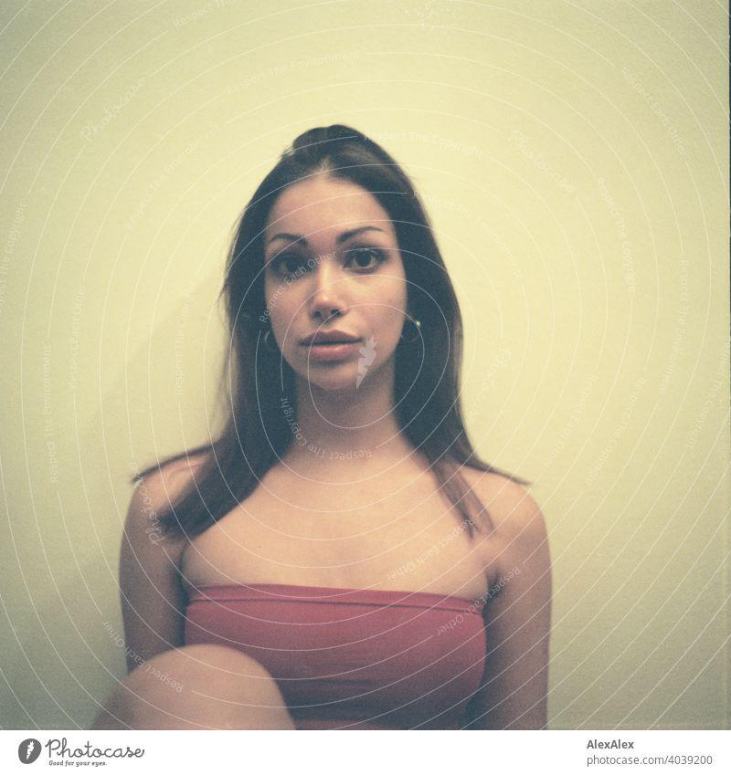 Analoges, rechteckiges Portrait einer jungen, schlanken, schönen Frau mit rotem Top anmutig seitlich dunkel Schönheit verliebt Dekolleté aufwärts Haut Freunde