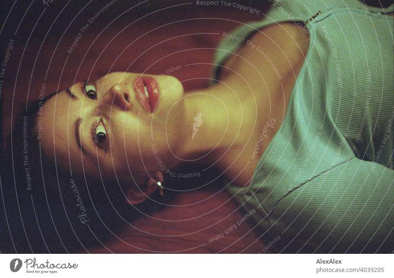 analoges Portrait einer jungen, schönen Frau die auf einem Holztisch liegt jugendlich Gesicht Identität ästhetisch Körnung Liebe erwartungsvoll Top Anmut