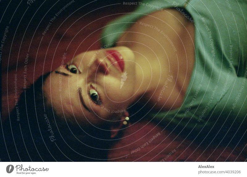 Analoges Überkopf- Portrait einer jungen, schlanken, schönen Frau die auf einem Holztisch liegt anmutig seitlich dunkel Schönheit verliebt liegen Dekolleté