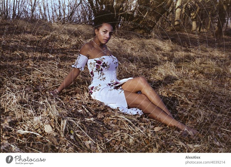 Junge Frau sitzt in der Natur und schaut skeptisch in die Kamera - analoges  Portrait sportlich dunkelhaarig langhaarig hübsch stark zierlich natürlich lockig