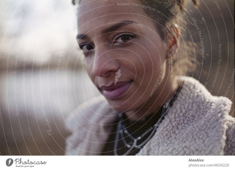 Junge Frau steht in der Natur an einem See  - analoges  Portrait sportlich dunkelhaarig langhaarig hübsch stark zierlich natürlich lockig schlank Aus Schmuck