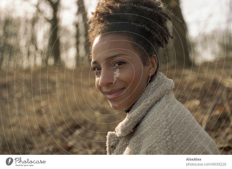 Junge Frau steht in der Natur an einem See und lächelt - analoges  Portrait sportlich dunkelhaarig langhaarig hübsch stark zierlich natürlich lockig schlank Aus