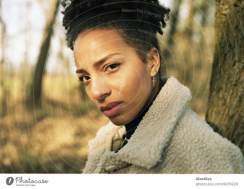 Junge Frau steht in der Natur und schaut skeptisch in die Kamera - analoges  Portrait sportlich dunkelhaarig langhaarig hübsch stark zierlich natürlich lockig
