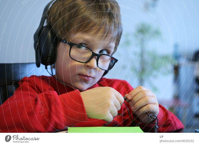 Kind mit Brille und Kopfhörer schaut sehr ernst von der Kamera weg skeptisch Zweifel Unsicherheit Kindheit Realität Experiment Hintergrundbild Idee abstrakt