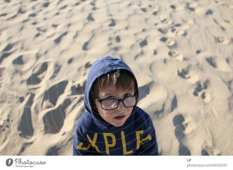 schönes Kind mit Brille und Kapuzenpulli schaut sehr ernst in die Kamera verwirrt ratlos skeptisch Skepsis Zweifel hestitate Unsicherheit Verwirrung Kindheit