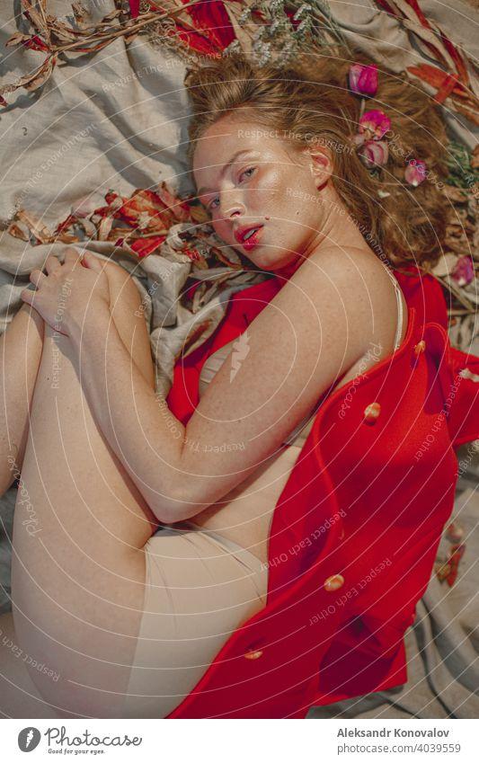 Junge rothaarige Frau in beiger Unterwäsche liegt auf grauem Leinenstoff unter orangefarbenem Mantel mit Blumen im Haar Schönheit Behaarung Sommersprossen nackt