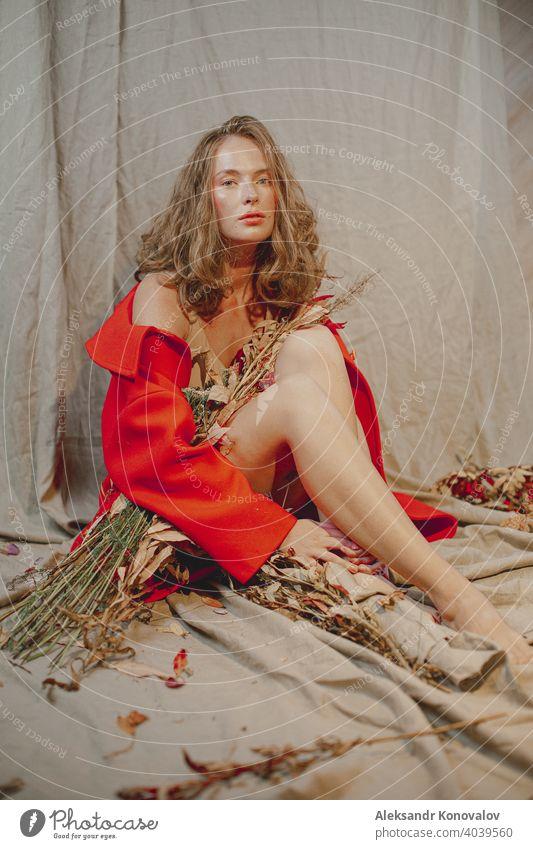Junge rothaarige Frau sitzt auf grauem Leinenstoff unter orangefarbenem Mantel mit Blumen und Vogelbeeren Schönheit Behaarung Sommersprossen nackt Junge Frau