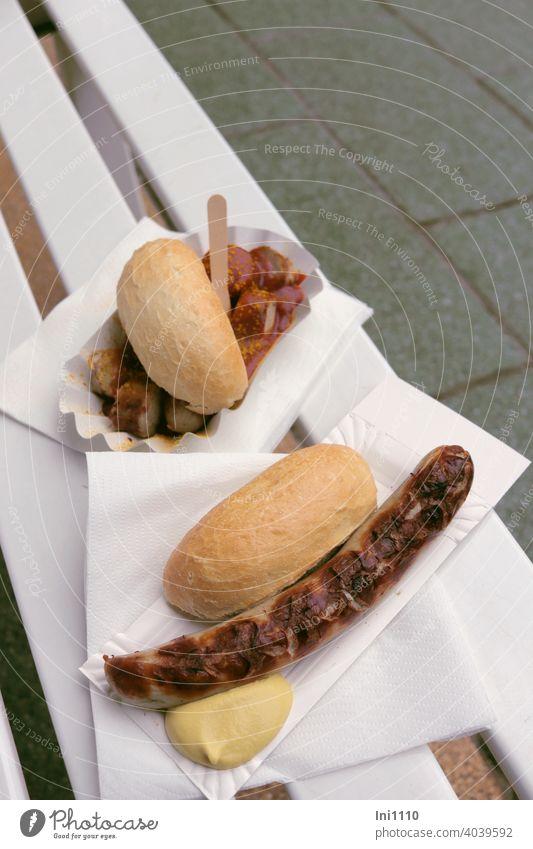 eine Bratwurst und eine Currywurst bitte Brötchen Senf Holzspieß Currysoße Servietten Gartenbank Sitzbank Pflastersteine Appetit & Hunger appetitlich heißhunger