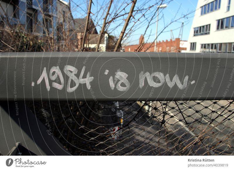 1984 is now schriftzug an brückengeländer graffiti streetart politisch überwachung dystopie dystopisch überwachungsstaat totalitär totalitarismus diktatur