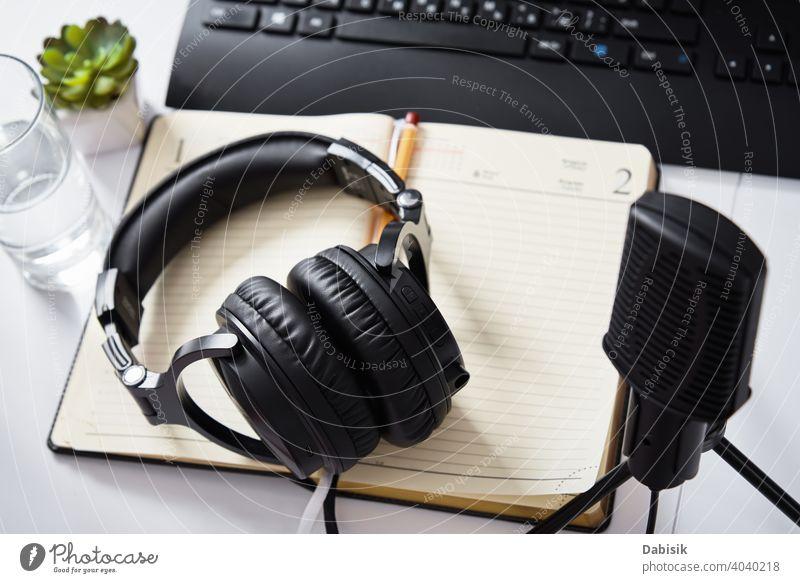 Mikrofon und Kopfhörer auf dem Tisch, Ansicht von oben. Radio-Podcast-Arbeitsplatz Audio online Technik & Technologie Draufsicht Keyboard abgelegen Bildung