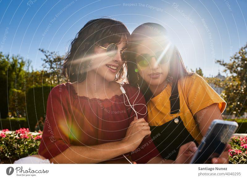 Zwei Teenager-Mädchen schauen auf das Telefon. Madrid jung Menschen Freundschaft Freunde Lifestyle schön Spaß Glück Zusammensein Freizeit Frau Lächeln