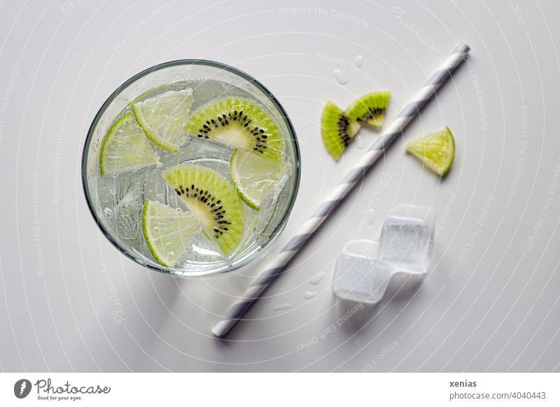 Aromatisiertes Erfrischungsgetränk mit Kiwi, Limette und Eiswürfel. Trinkhalm aus Papier liegt bereit. Getränk Sommer Detox Aromawasser Obst Frische