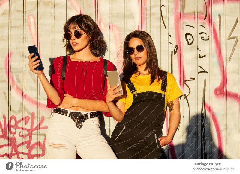 Zwei Teenager-Mädchen stehen und schauen auf ihr Smartphone Madrid jung Menschen Freundschaft Freunde Lifestyle schön Spaß Glück Zusammensein Freizeit Frau