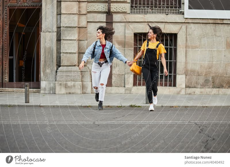Zwei Teenager-Mädchen laufen die Straße hinunter. Madrid jung Menschen Freundschaft Freunde Lifestyle schön Spaß Glück Zusammensein Freizeit Frau Lächeln