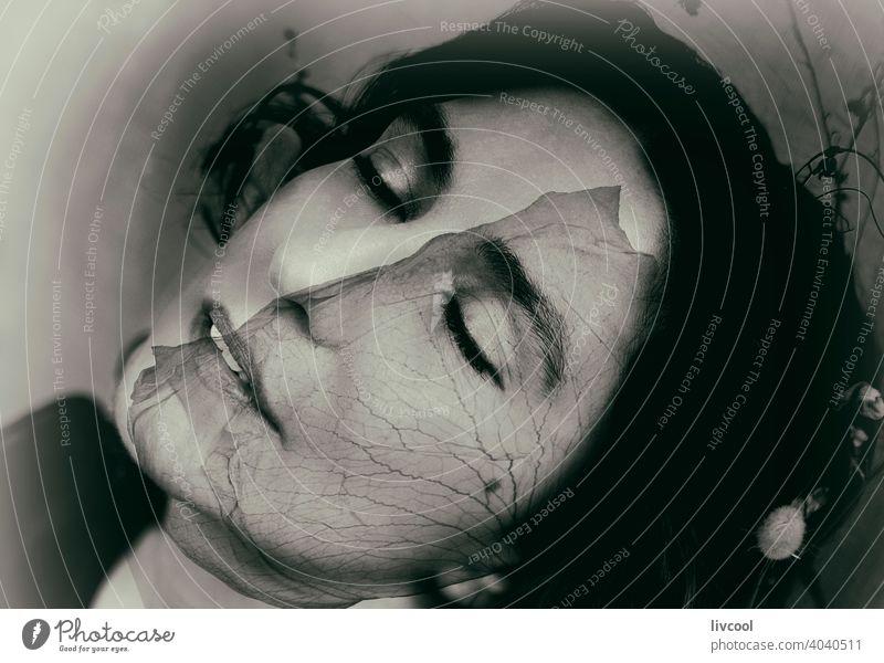 Frau mit melancholischer Haltung und Rosenblüte brünett Kräusel Sommersprossen Schönheit Rosenblatt reif Porträt echte Menschen Lifestyle attraktiv Licht Reife