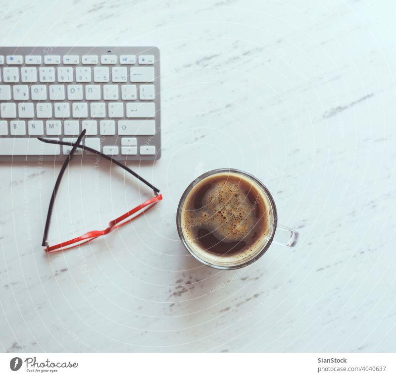 Arbeitsplatz mit Brille, Kaffee und Tastatur. Laptop Top Schreibtisch Ansicht Tisch Büro Computer Tasse Desktop weiß Keyboard oben Business Hintergrund Raum