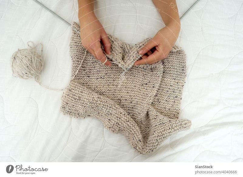 Nahaufnahme der Hände einer jungen Frau, die einen Schal strickt stricken Hand Wolle Handwerk Nadel Pullover Muster Mode warm Bekleidung Finger Garn Schnur