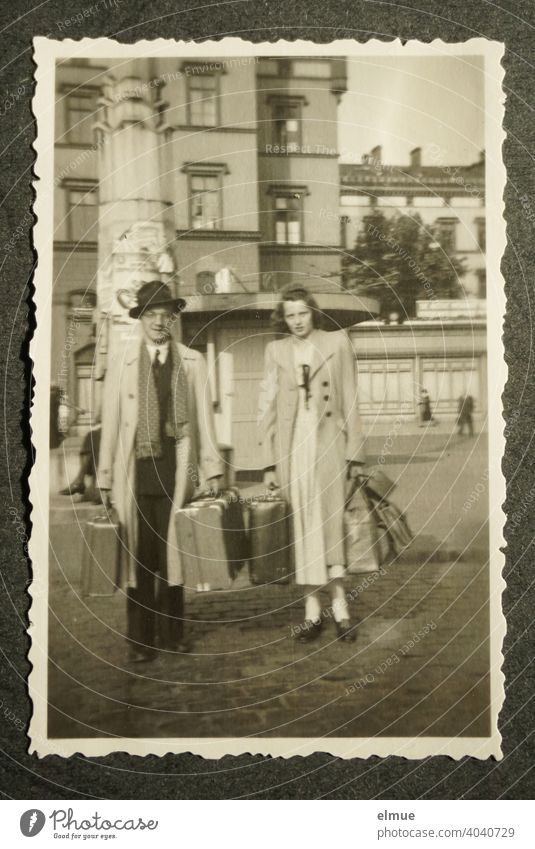 Schwarz-Weiß-Foto mit Büttenrand aus den 1950er Jahren auf einer schwarzen Fotoalbumseite, ein junges Paar mit Reisekoffern zeigend / Urlaubsreise / Erinnerungen / analoge Fotografie