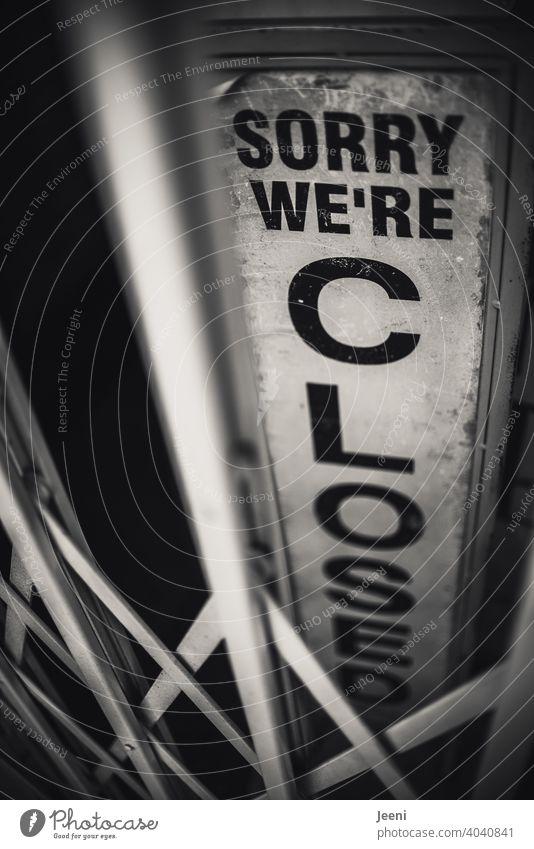 Immer noch Lockdown im Einzelhandel, in der Gastronomie und Hotellerie | Ein Schild eines Geschäfts hinter einer verschlossenen Gittertür - schwarze Aufschrift auf hellem Untergrund: sorry we're closed I Entschuldigung, es ist geschlossen I corona thoughts
