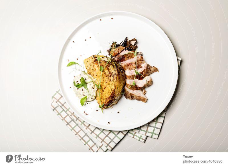Draufsicht Entenbrust mit Krautsteak mit Käsesauce. Leckeres Restaurant Gericht auf einem runden Teller auf einer karierten Serviette Brust Kohlgewächse Steak