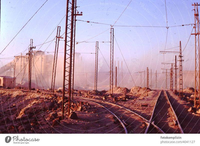 Bahnschienen auf Fabrikgelände in der Wüste Schienen fabrik industriegebiet Industrie Elektrizität Leitung Kabel Technik & Technologie Hochspannungsleitung