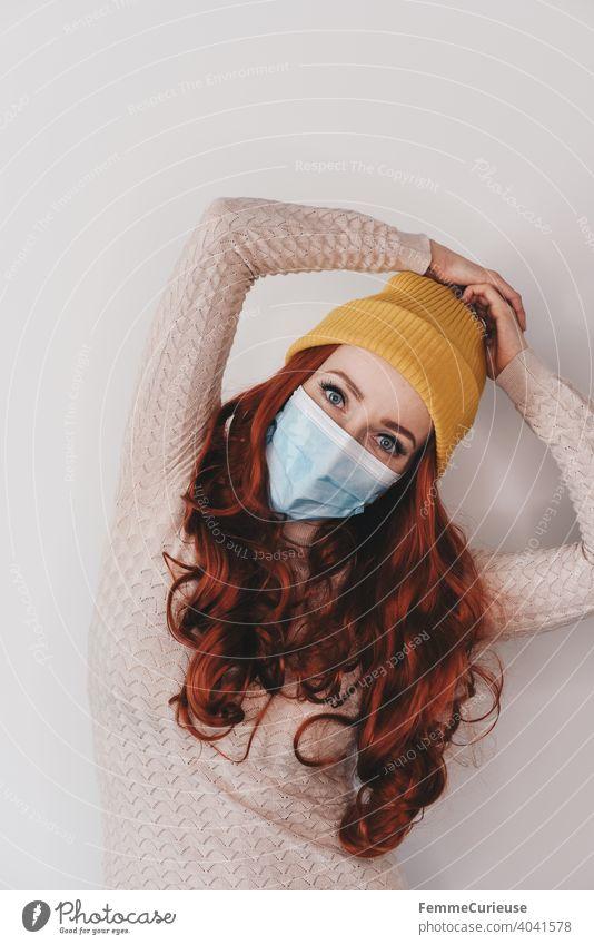 Junge rothaarige Frau mit gelber Hipster Beanie Mütze und medizinischer Schutzmaske Maske posiert mit beiden Armen über Kopf posierend lockiges haar Junge Frau