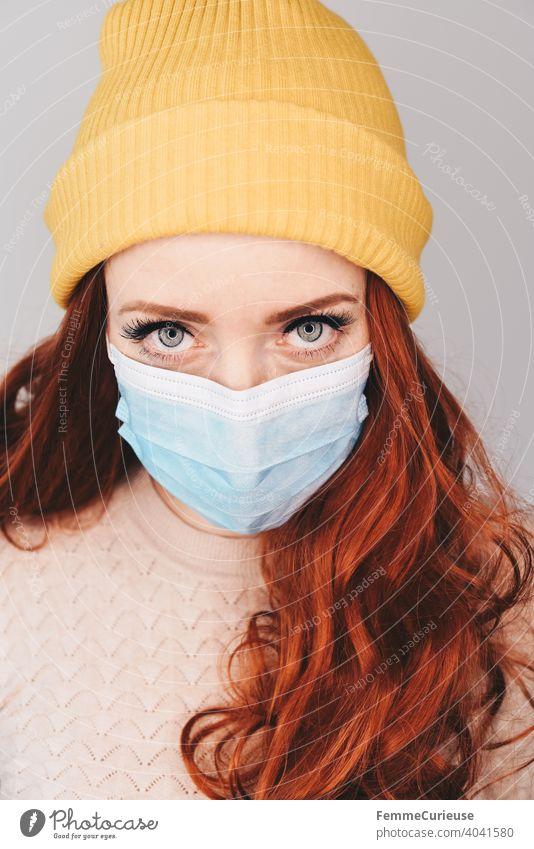 Junge rothaarige Frau mit gelber Hipster Beanie Mütze und medizinischer Schutzmaske Maske schaut mit eindringlichem Blick in Kamera (Portrait)